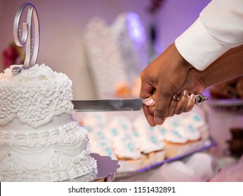 An African American couple cuts a white wedding cake at their wedding