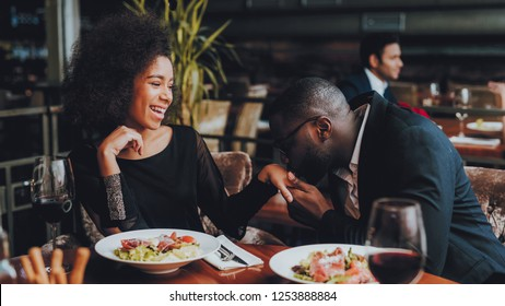 African American Couple Dating in Restaurant. Romantic Couple in Love Dating. Cheerful Man and Woman with Menu in a Restaurant Making Order. Romantic Concept. Man Kissing Girls Hand.