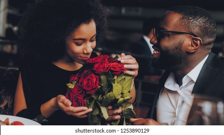 Couple afro-américain mangeant au restaurant. Couple romantique en amour. Cutel Man and Girl in a Restaurant Making Order. Concept romantique. Un homme donnant un bouquet de fleurs. Roses Rouges.