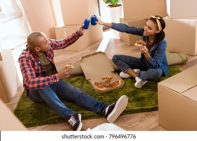 african american couple eating pizza and clinking with soda cans in new apartment with cardboard boxes