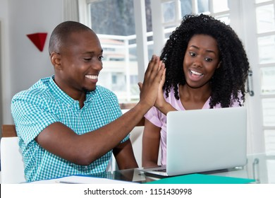 African american couple making online reservation with laptop at desk at home