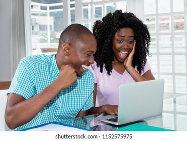 African american couple shopping presents and gifts online with laptop at desk at home