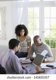 African American couple sitting at dining table with financial advisor