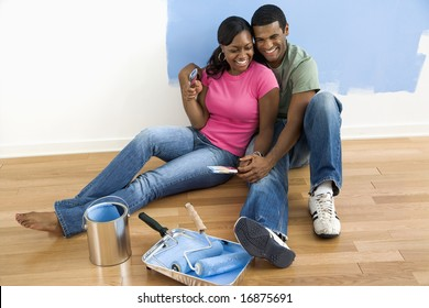 African American couple sitting together relaxing next to half-painted wall and painting supplies