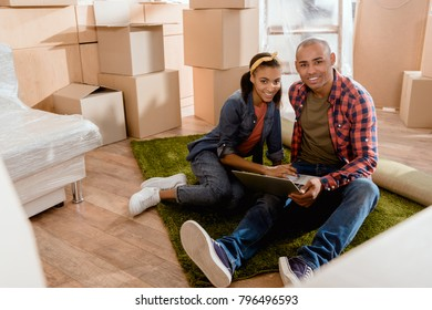 african american couple using laptop in new apartment with cardboard boxes