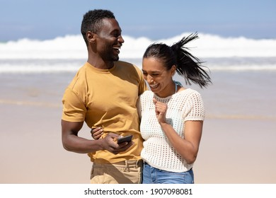 African american couple using smartphone on a beach by the sea. healthy lifestyle, leisure in nature.