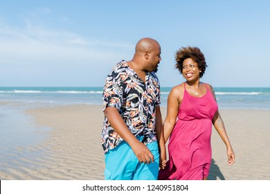 African American couple walking at the beach