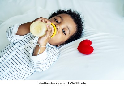 African american cute baby boy drinking milk from bottle and sleeping on bed with a red heart at home, Children need love and caring