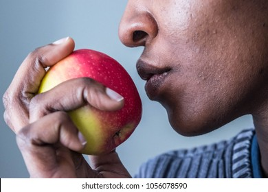 African American Dark woman eating biting a pink lady apple, isolated against white background healthy eating weight loss concept.   Adam and Eve. Forbidden