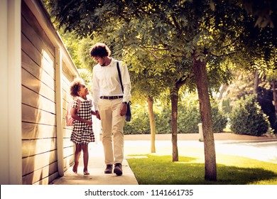 African American daughter and her father walking trough city park and talking.