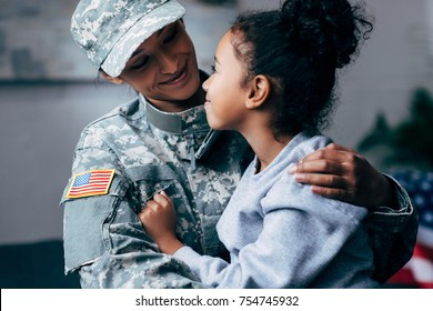 african american daughter hugging mother in military uniform at home
