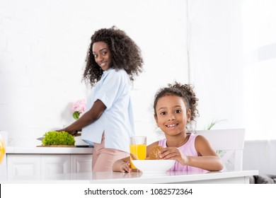 african american daughter with orange juice and cookies on kitchen with mother