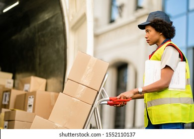 African American delivery woman with hand truck unloading packages from a truck.