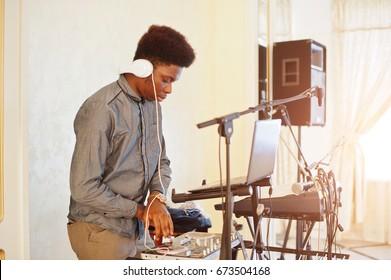 African american dj in huge white headphones creating music on mixing panel.