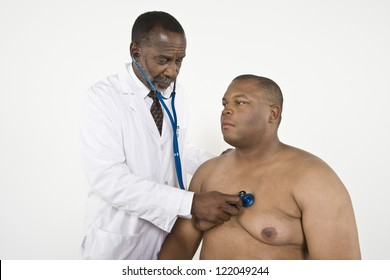 An African American doctor checking blood pressure of a patient in clinic