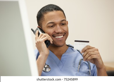 African American doctor on the phone sitting at the computer looking at his credit card
