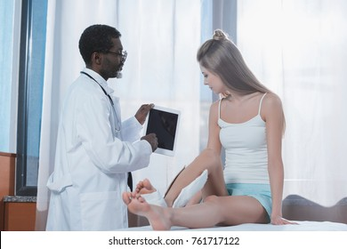 african american Doctor showing something on tablet to patient
