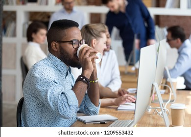 African American employee drinking coffee and talk on phone while working at computer in shared office, black male worker speak on cell, consulting client or chatting with friend, busy with pc