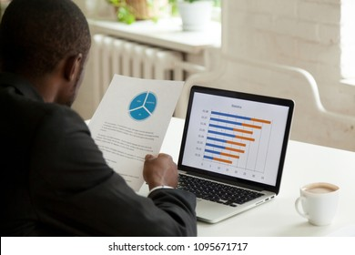 African American employee holding handout with presented diagram, comparing financial data with statistics at laptop screen, analyzing business success and raising income. Back view over the shoulder