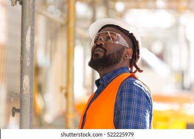 Afroamerykanin inżynier patrząc w górę wśród rusztowań