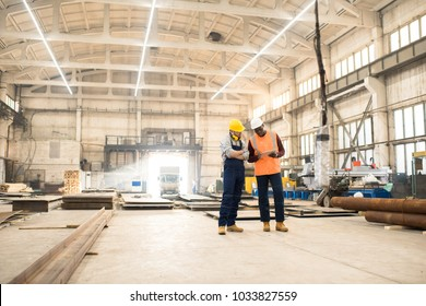 African American engineer wearing reflective vest and hardhat using digital tablet while discussing joint work with his colleague, interior of spacious production department of plant on background