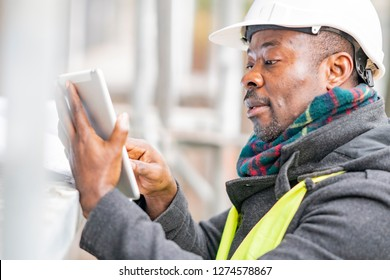 African American engineer wearing safety helmet and jacket checking documents on tablet computer on construction site