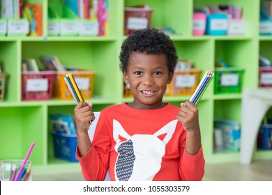 African American ethnicity kid holding group of color pencil smiling at library in kindergarten preschool classroom.education concept