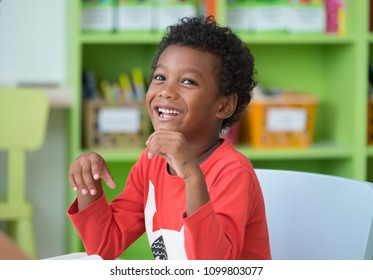 African American ethnicity kid smiling at library in kindergarten preschool classroom.happy emotion.education concept