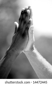 """african american and European american men do a """"high five"""" hand clap outside in black and white"""