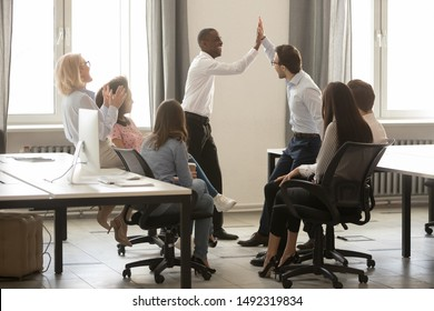 African American executive, team leader with colleague giving high five during briefing, smiling employees engaged in team building activity, celebrating achievement, business win or good result