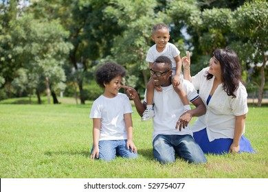 African American family alongside with Asian mum being playful and having good times in the park.
