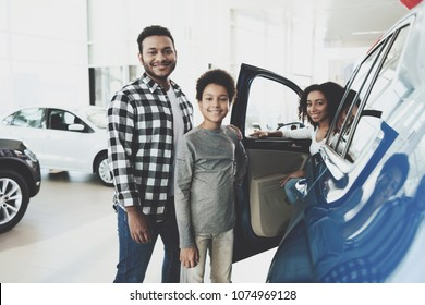 African american family at car dealership. Father, mother and son posing near new blue car.