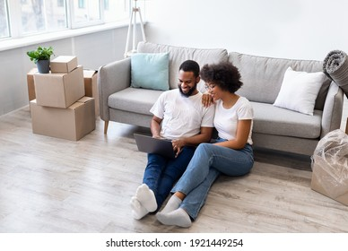 African American Family Couple Using Laptop After Moving In New House, Browsing Internet Sitting On Floor Among Packed Boxes. Renting Apartment Online Service, Real Estate Agency Website Advertisement