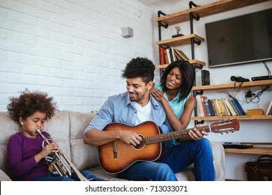 African american family enjoying playing musical instruments together at home.