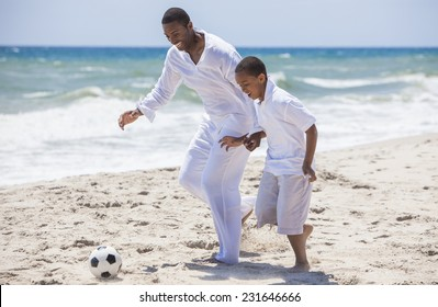 African American family of father and son, man & boy child, having fun playing football soccer in the sand on a sunny beach