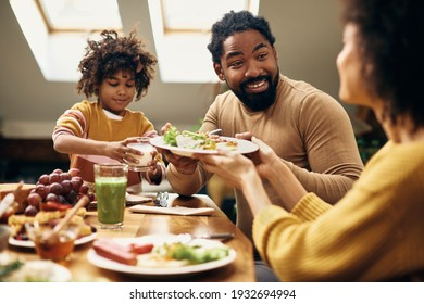 African American family having a meal together at dining table. Focus is on happy man.