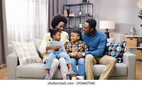 African American family with kids sitting on sofa in room, looking at camera and smiling, positive emotions, parents with children gathered together at home parenting concept
