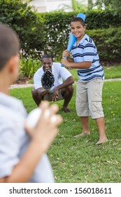 African American family, man, & boy children, father & two sons playing baseball together outside.