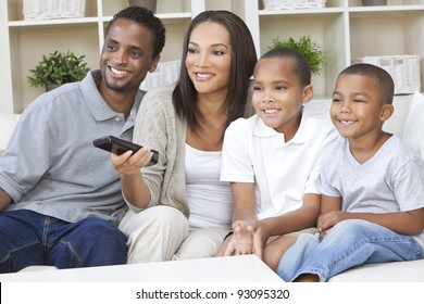 African American family, mother & father parents and two sons, having fun watching television together using the remote control