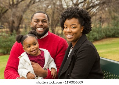 African American Family playing and laughing with their daughter.