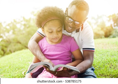 African American family reading a book together in the outdoor park