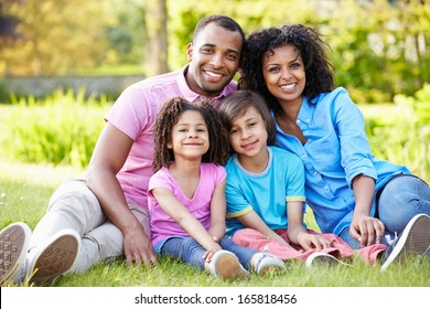 African American Family Sitting In Garden