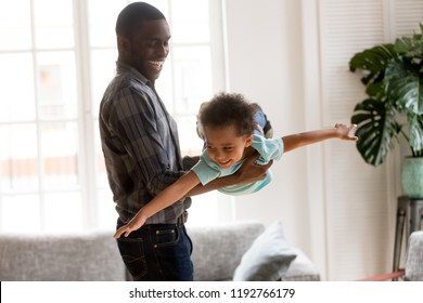 African American family spend time together have a fun standing in living room at home. Laughing father holding on hands flying smiling cute little preschool toddler son. Happy black family concept