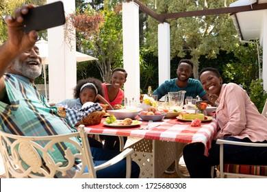 La famille afro-américaine passe du temps ensemble dans le jardin par beau temps, assise près d'une table et déjeunant, tandis qu'un homme âgé prend un selfie avec son smartphone.