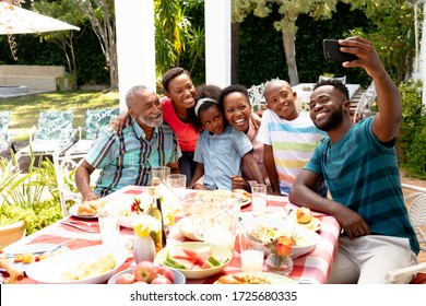 African American family spending time together in the garden on a sunny day, sitting by a table and having a lunch, while a man is taking a selfie with his smartphone.  - Shutterstock ID 1725680335