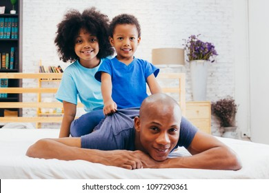 African American family of three, kids sitting on father's back at home
