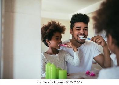 African american family washing teeth in the bathroom.