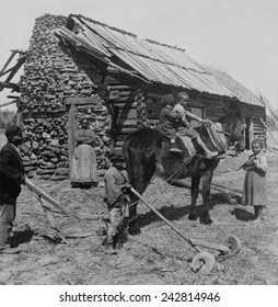 African American farm family outside their log cabin home in North Carolina. Rural poverty persisted for several decades following abrupt emancipation of slaves in a post-Civil War South. Ca. 1903.