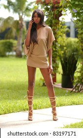 African American fashion model with sexy long legs in short dress standing with tropical trees on background