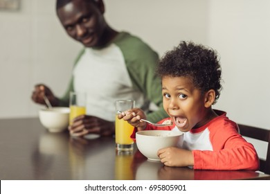 african american father and cute hungry son eating breakfast